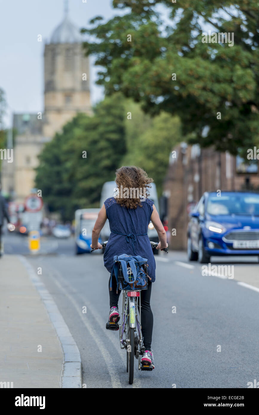 A young woman, possibly a student, cycles up St Aldate's in the university town of Oxford. Tom Tower of Christ - Stock Image