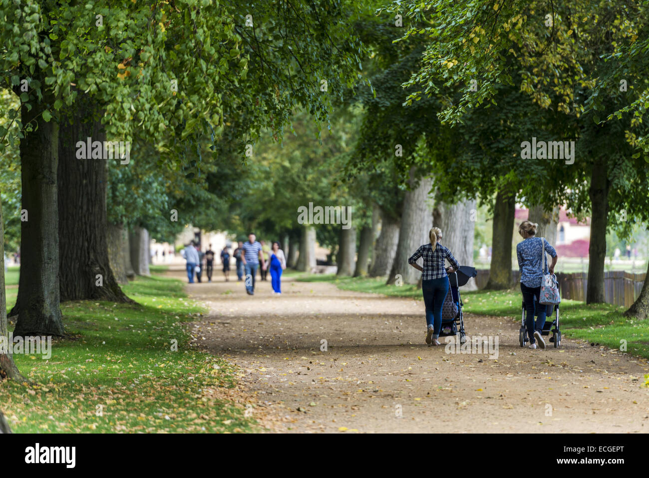 Two mums with pushchairs walk along a path in Christ Church meadow towards the college and Oxford - Stock Image