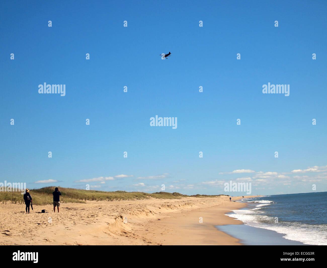 Bi Plane flying above a beach on Marthas Vineyard, Cape Cod, USA - Stock Image
