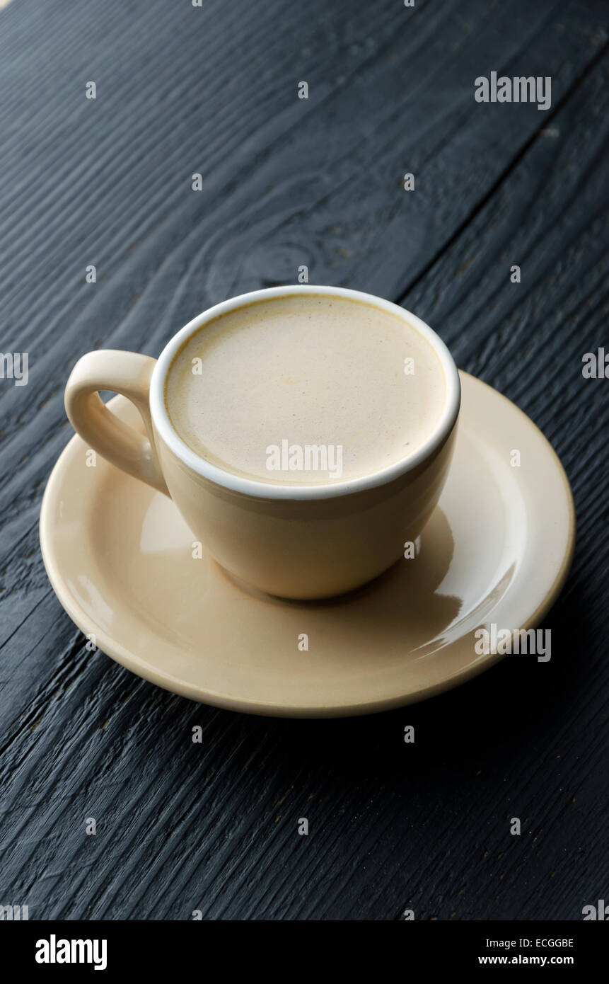 Cup of cappuccino over dark wooden table - Stock Image
