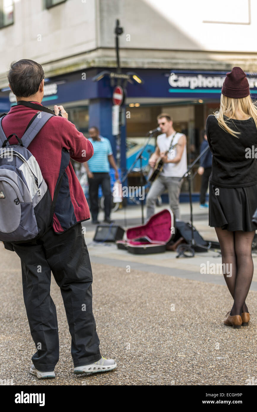 Passers by take picture of street entertainer young musicians on Cornmarket Street, Oxford - Stock Image