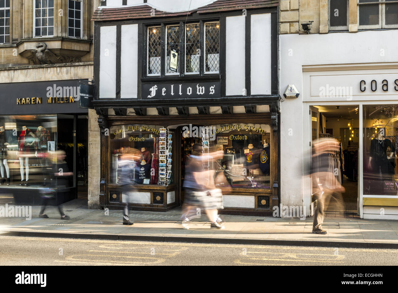 A long exposure of pedestrians passing Fellows College Store on the High Street, Oxford, UK - Stock Image