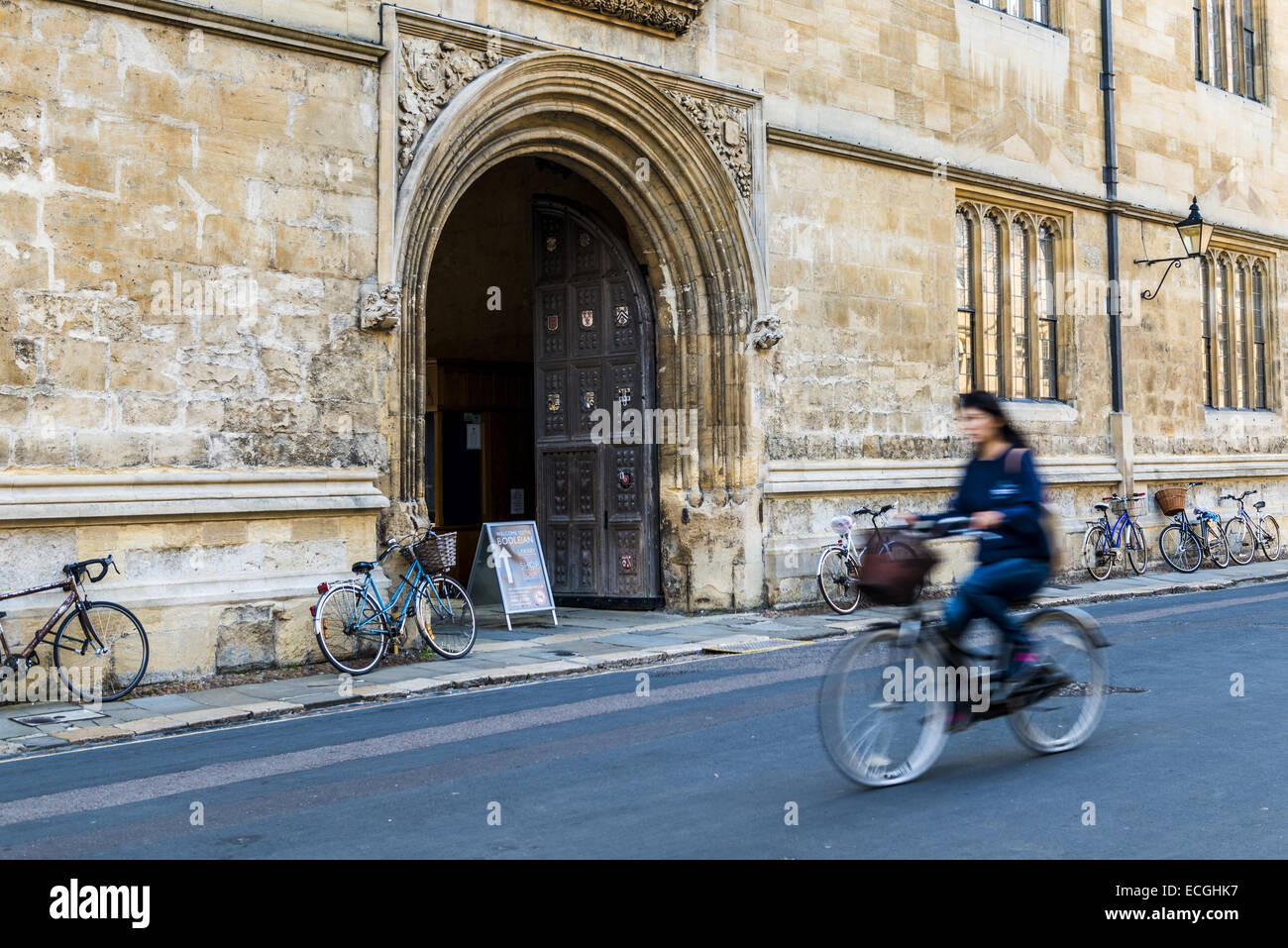 A cyclist passes the doorway to the Bodleian Library on Catte Street, the library of Oxford University - Stock Image