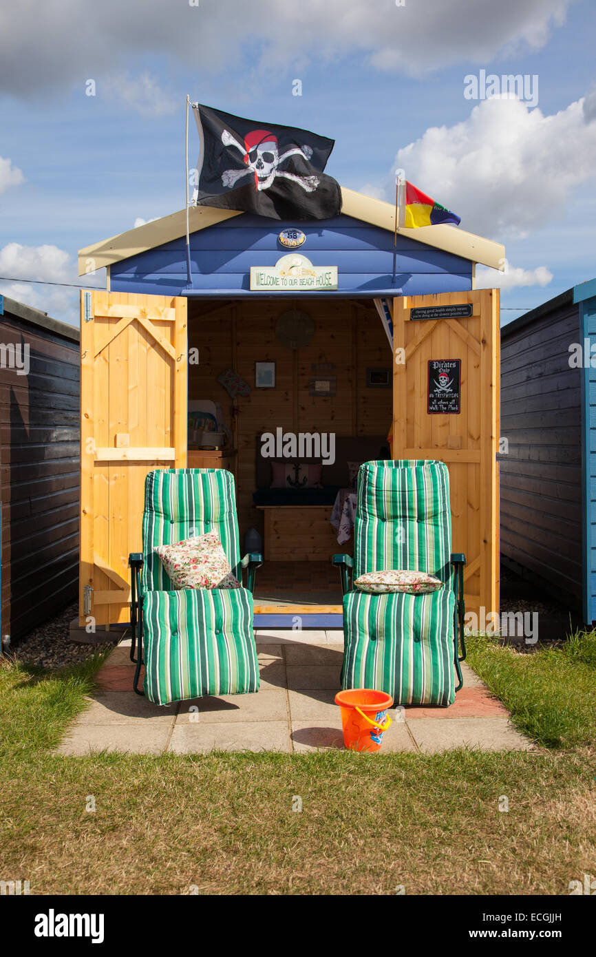 Beach hut with two reclining garden chairs, beach hut has a pirate flag flying from the roof - Stock Image