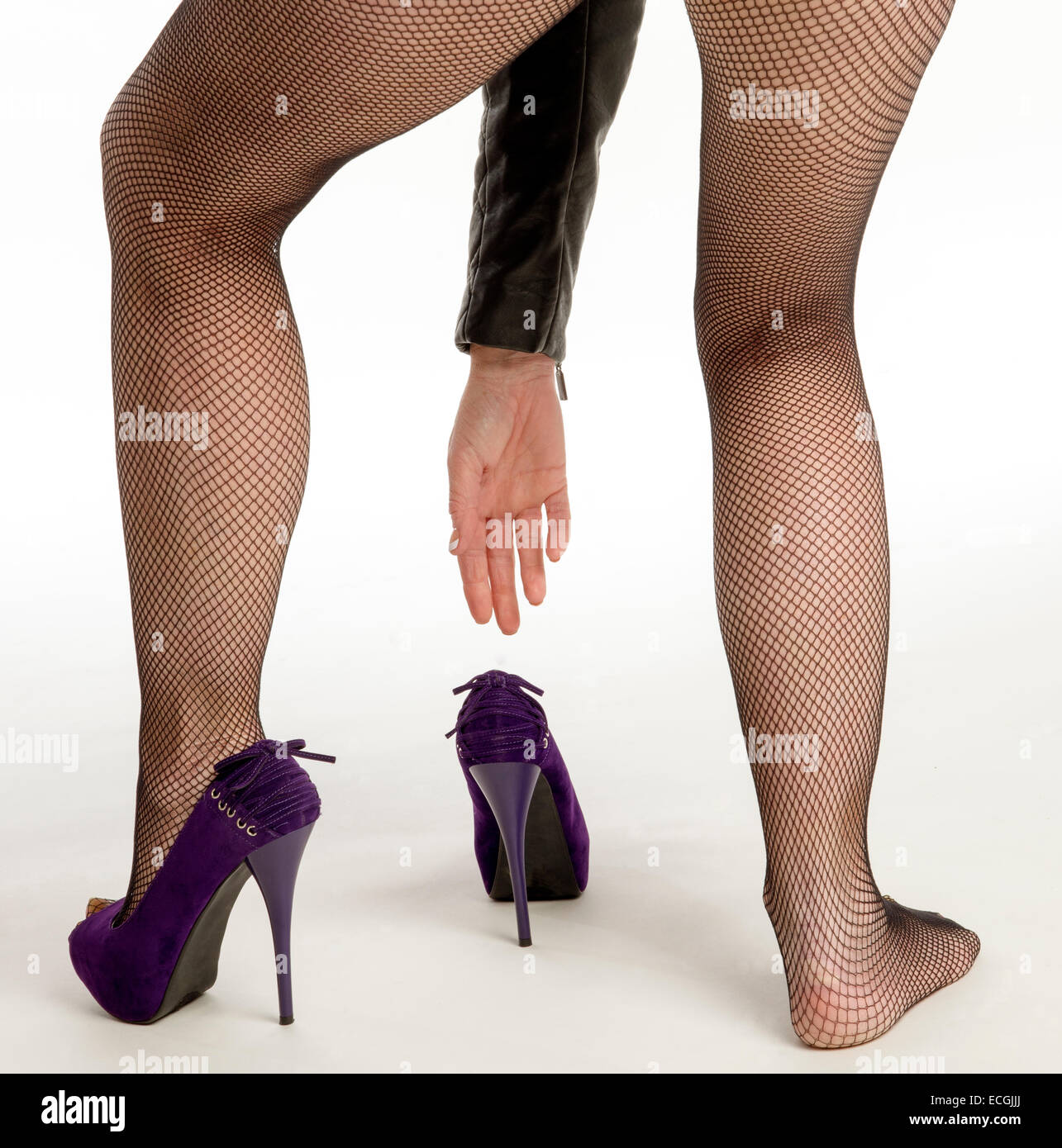 Woman putting on high heel shoes wearing black fishnet tights - Stock Image
