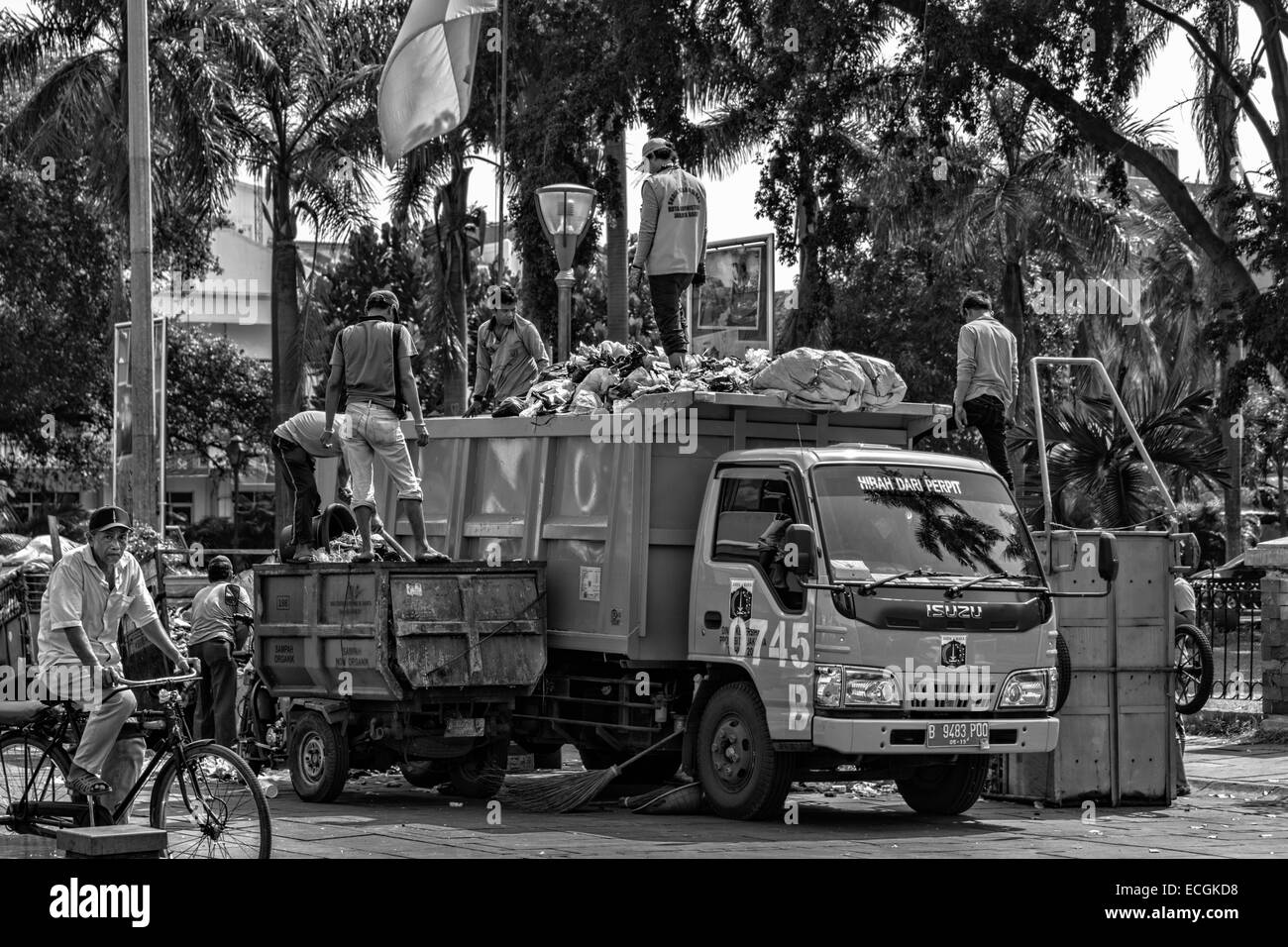 Street cleaners are cleaning up the rubbish that was left behind on Fatahillah Square, Jakarta, Indonesia. - Stock Image
