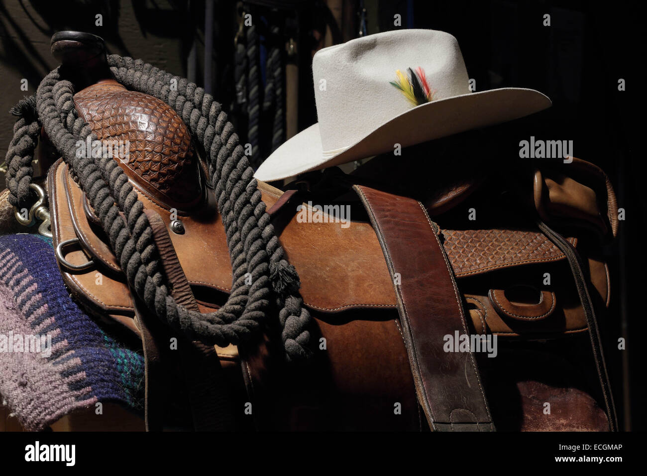 A low light still life photograph of a saddle and a Cowboy Hat - Stock Image