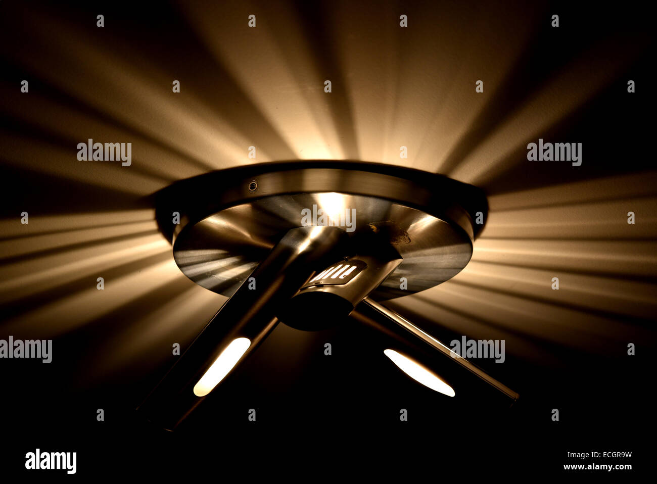 A modern light throws beams of light onto the ceiling - Stock Image