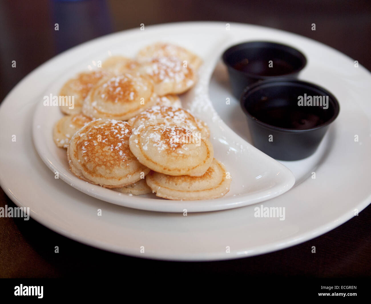 Bite-sized North American dollar pancakes, dusted with powdered sugar. - Stock Image