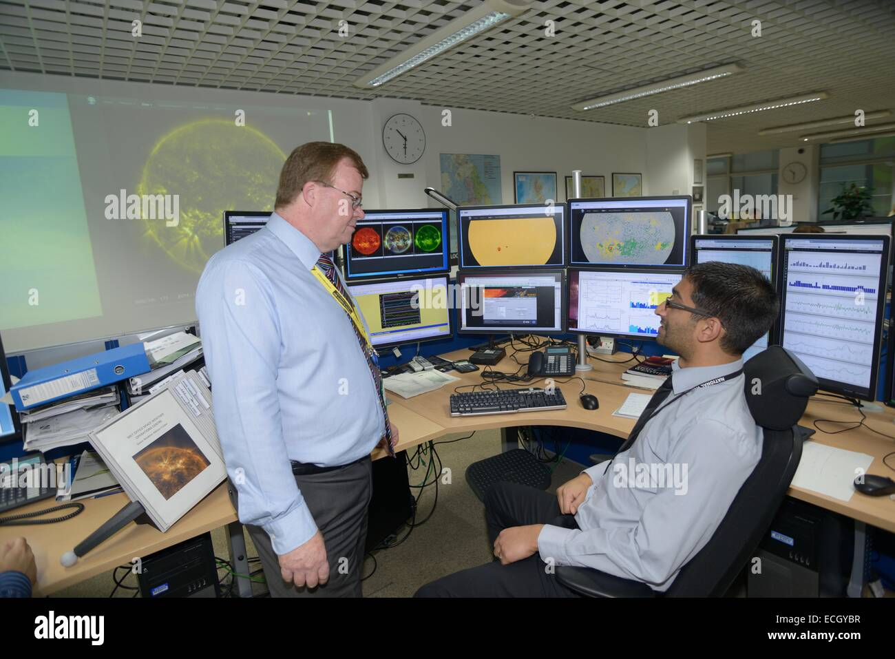 UK Met Office -  Mark Seltzer, Senior Operations Meterologist in the Space Weather Centre, with sun spot on Screens - Stock Image