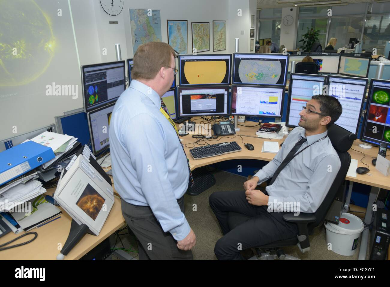 UK Met Office -  Mark Seltzer, Senior Operations Meteorologist in the Space Weather Centre, with sun spot on Screens - Stock Image