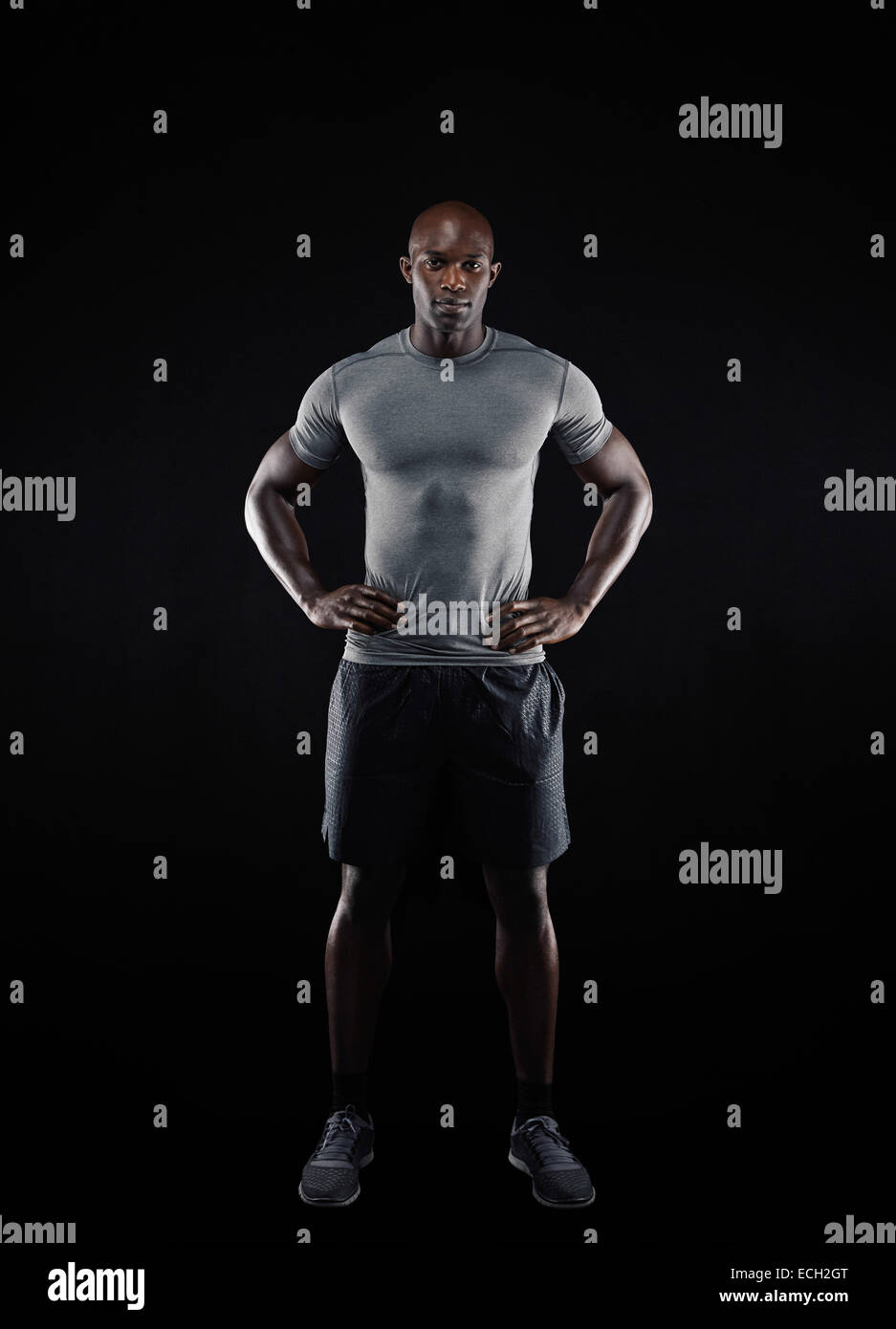 Full length portrait of muscular young man in sportswear looking at camera against black background. Strong African - Stock Image