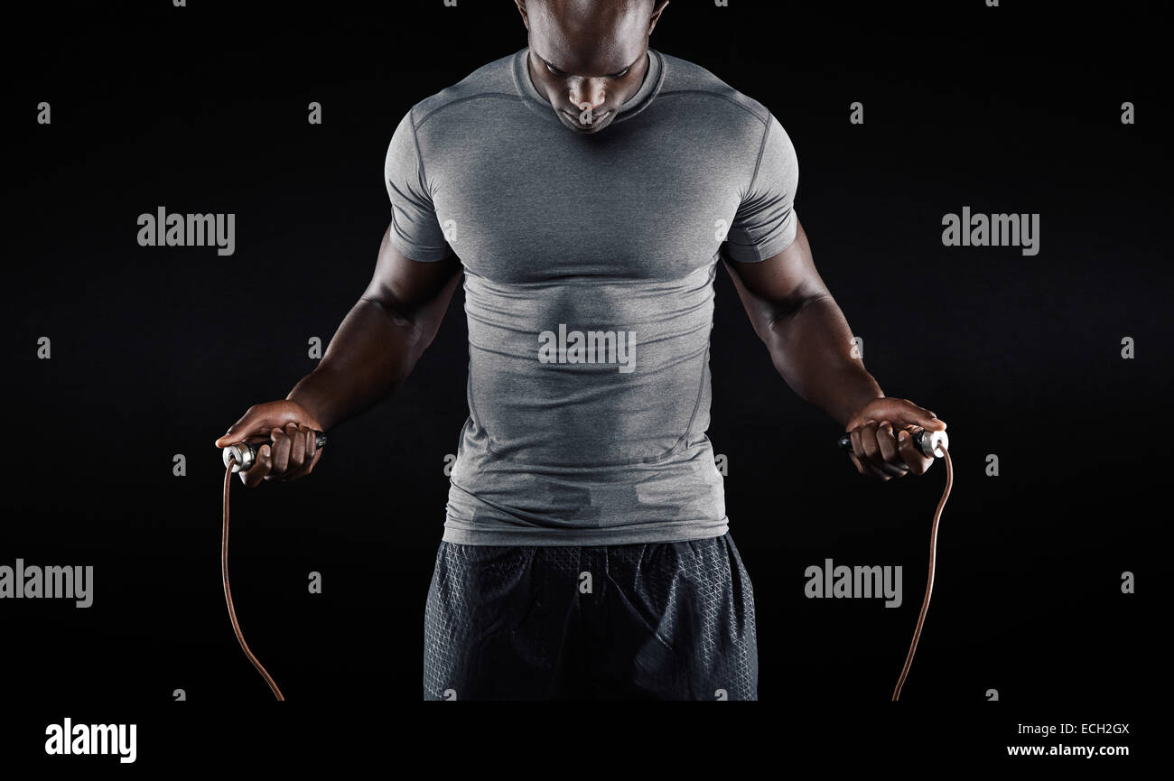 Muscular man skipping rope. Portrait of muscular young man exercising with jumping rope on black background - Stock Image