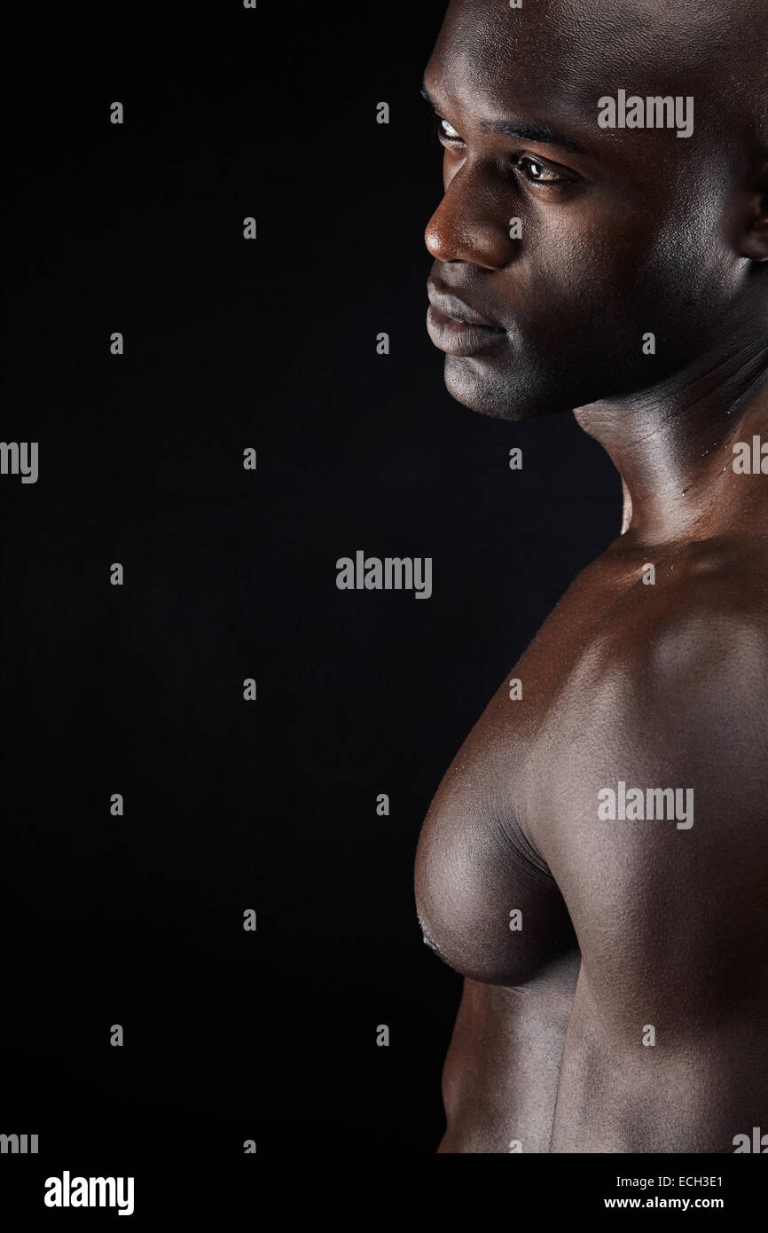 Cropped shot of a man standing shirtless in the studio. African male model with muscular build on black background - Stock Image