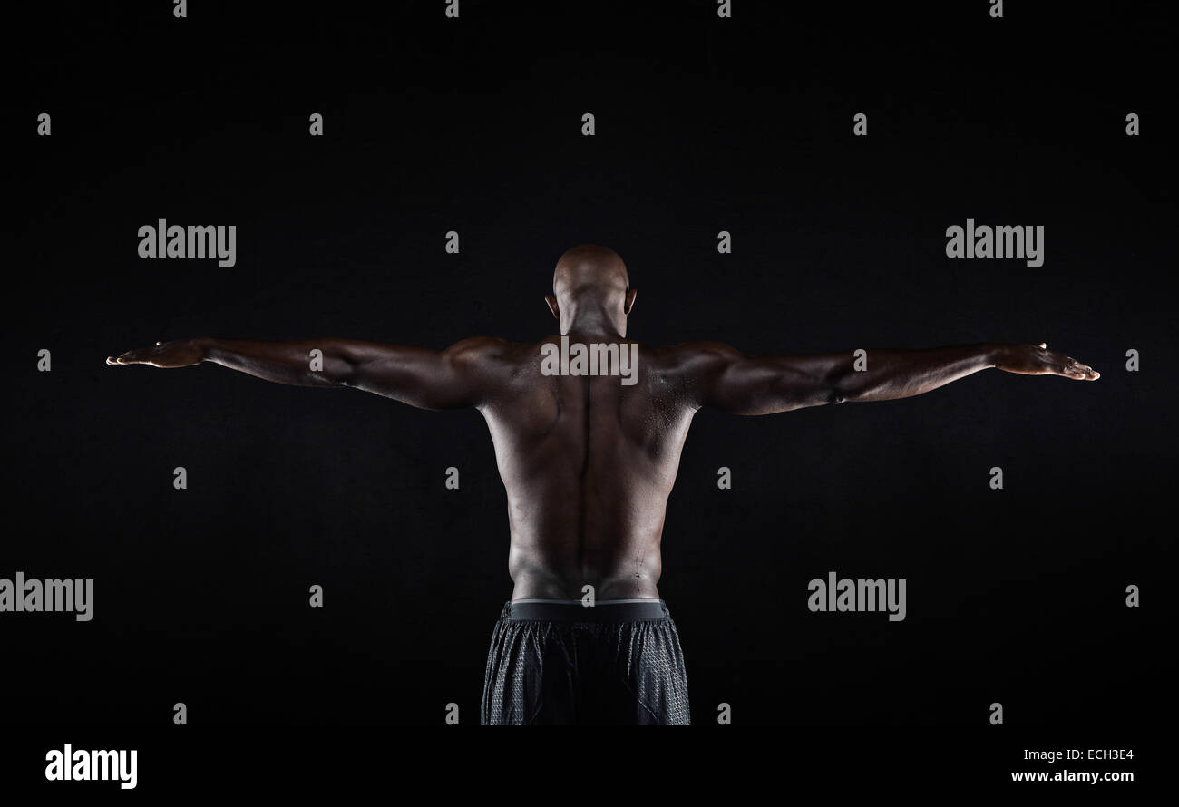 Portrait of a strong back of a African muscular man stretching his arms against black background. Rear view of fitness - Stock Image