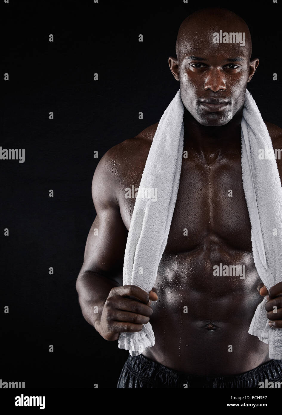 Young shirtless African man carrying towel on shoulders and looking at camera while standing against black background. - Stock Image