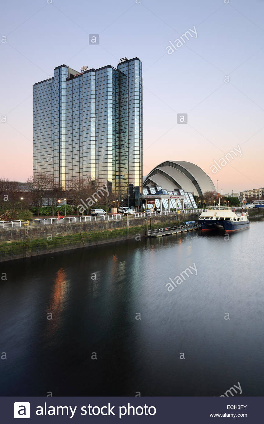 The Crowne Plaza hotel and Clyde auditorium in Glasgow reflecting on the River Clyde at Sunset. - Stock Image