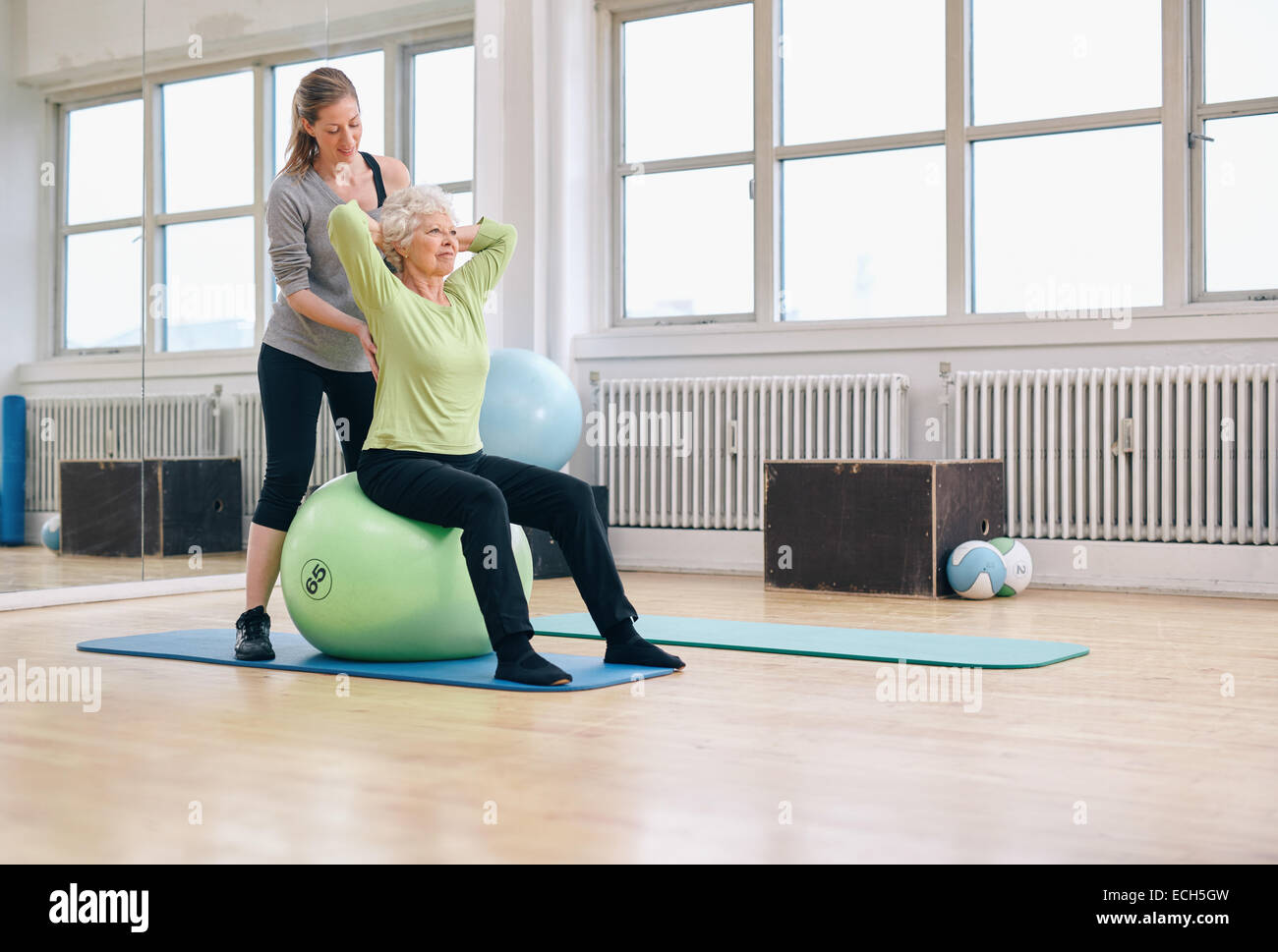Senior woman sitting on a pilates ball exercising at health club being assisted by her personal trainer. Physical - Stock Image