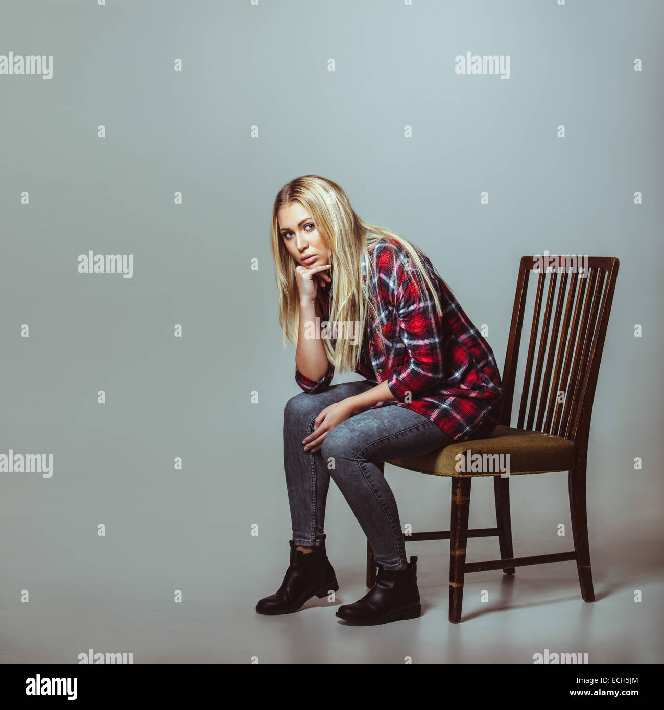Studio shot of young woman in casual outfit sitting on chair looking at camera. Caucasian female model with copyspace. - Stock Image
