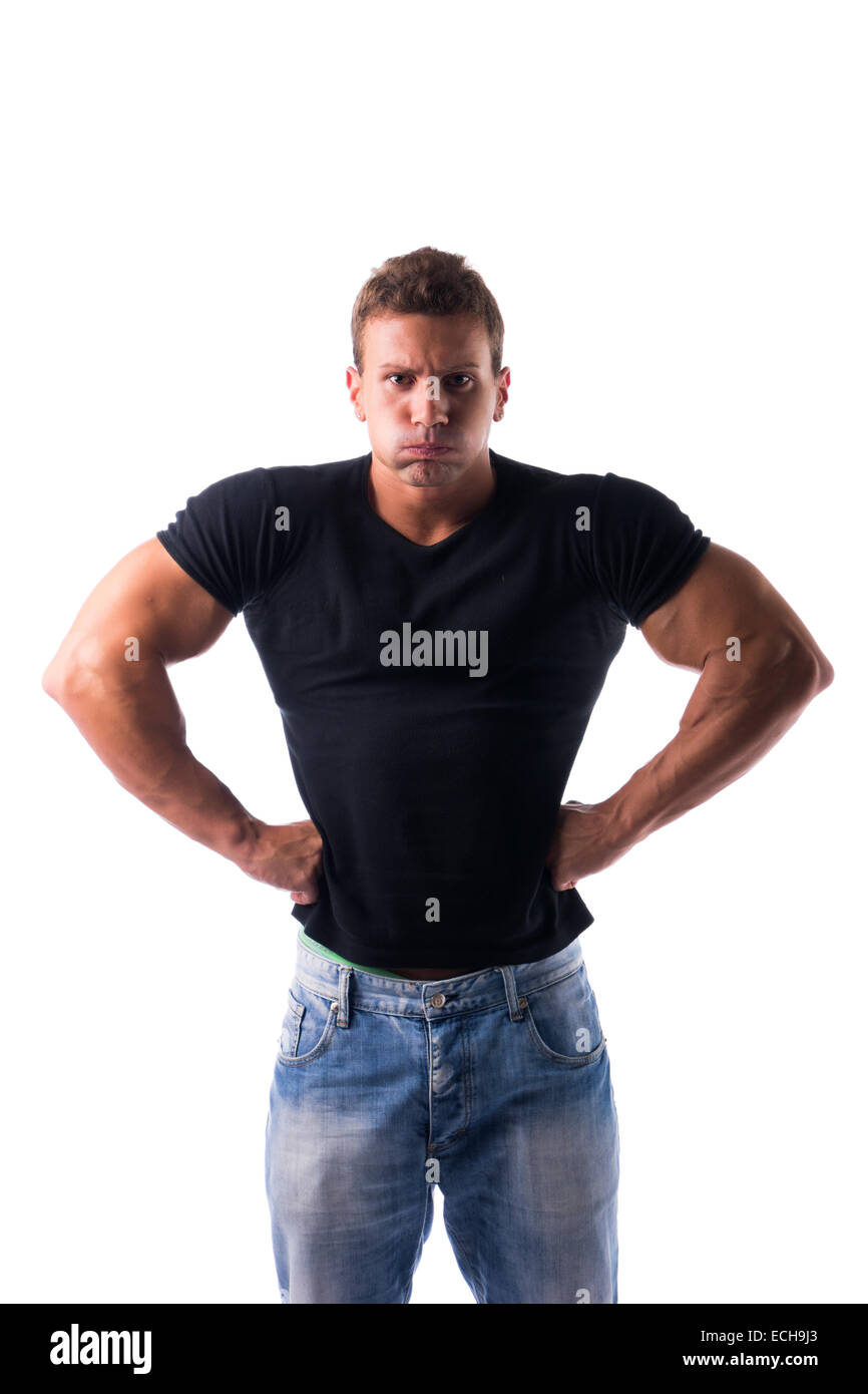 Angry muscular young man with fists on his hips looking at camera, isolated on white - Stock Image