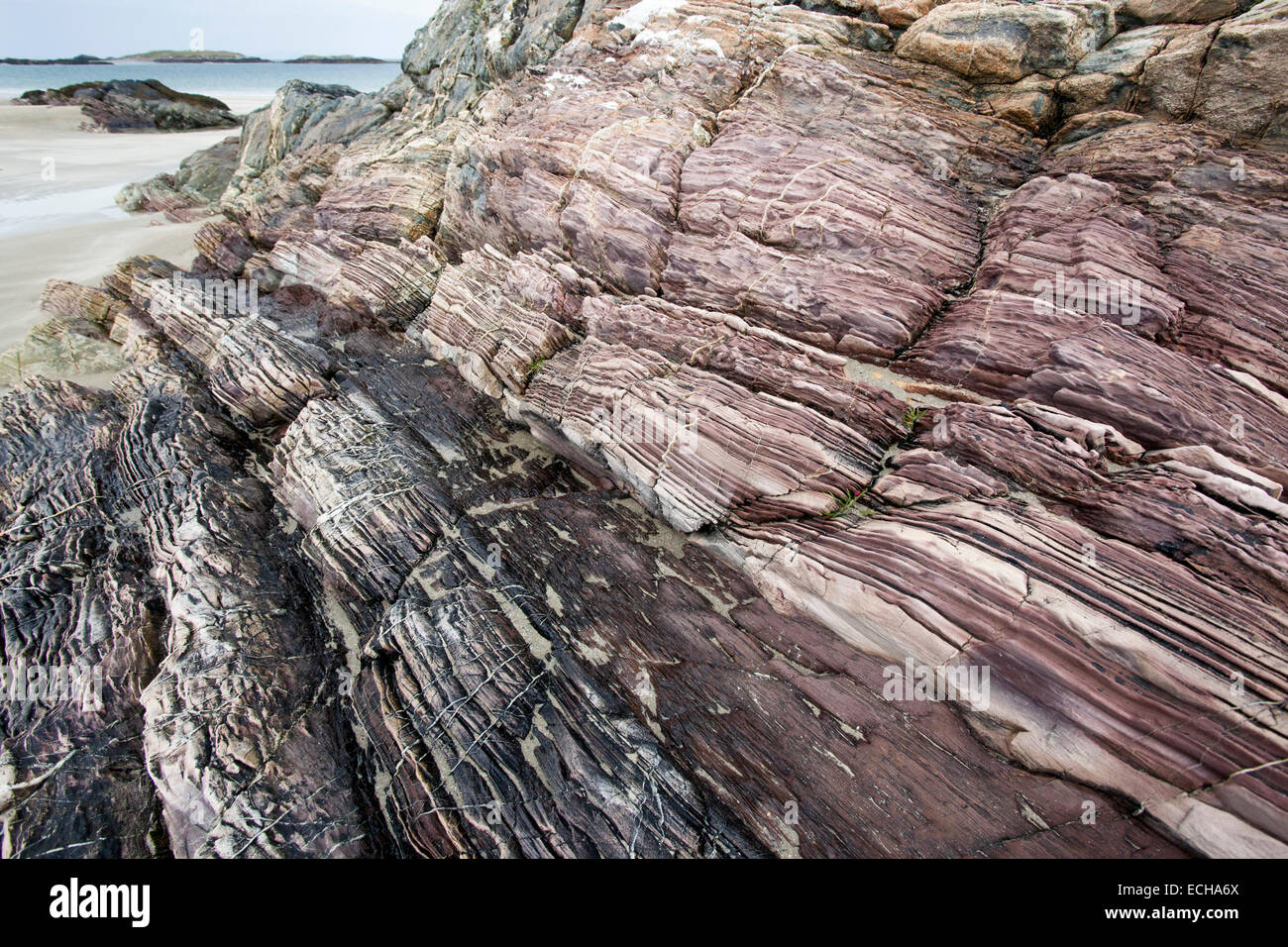 Layered red sandstone outcrop on Glassilaun Beach, Connemara, County Galway, Ireland. - Stock Image