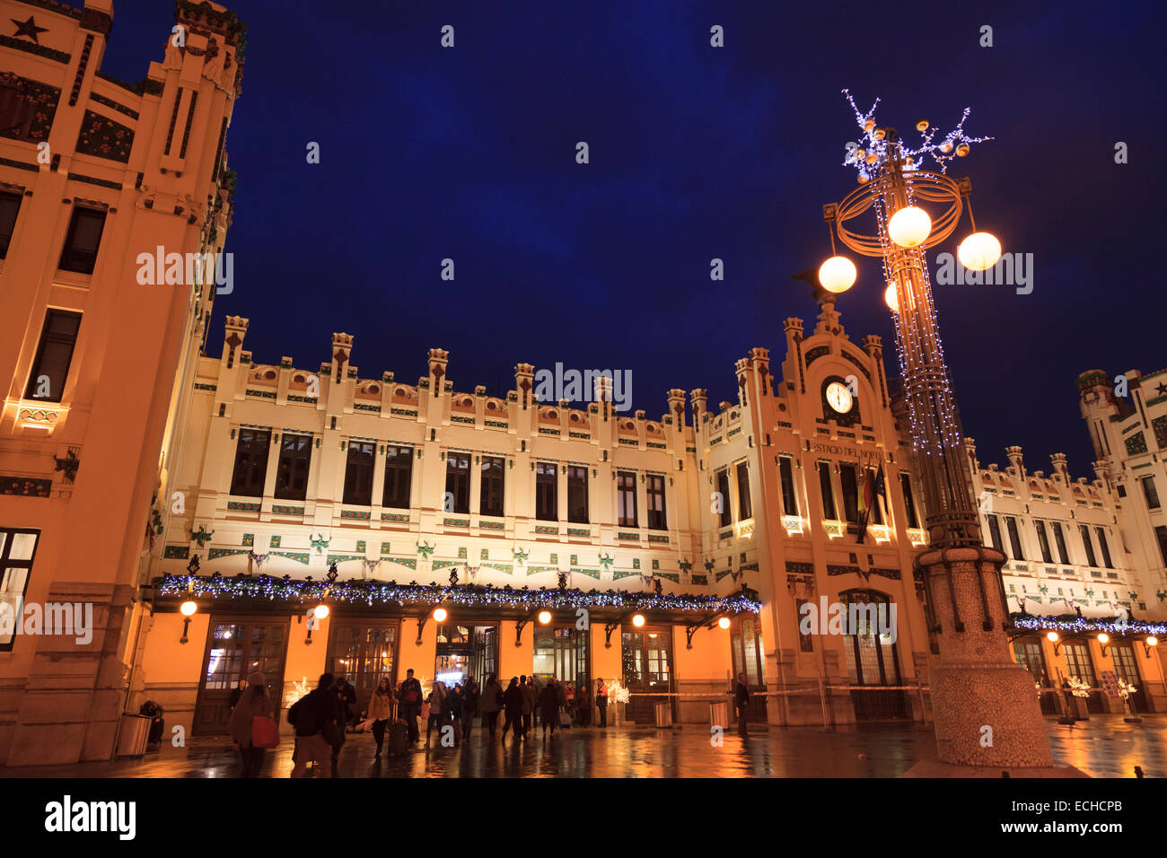 Travellers entering the exterior of the main railway station Estacio del Nord in Valencia lit up on a rainy night - Stock Image