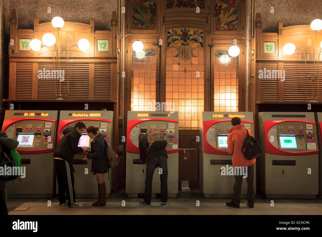Customers buying tickets at the machines in the ticket hall of the main railway station Estacio del Nord in Valencia - Stock Image