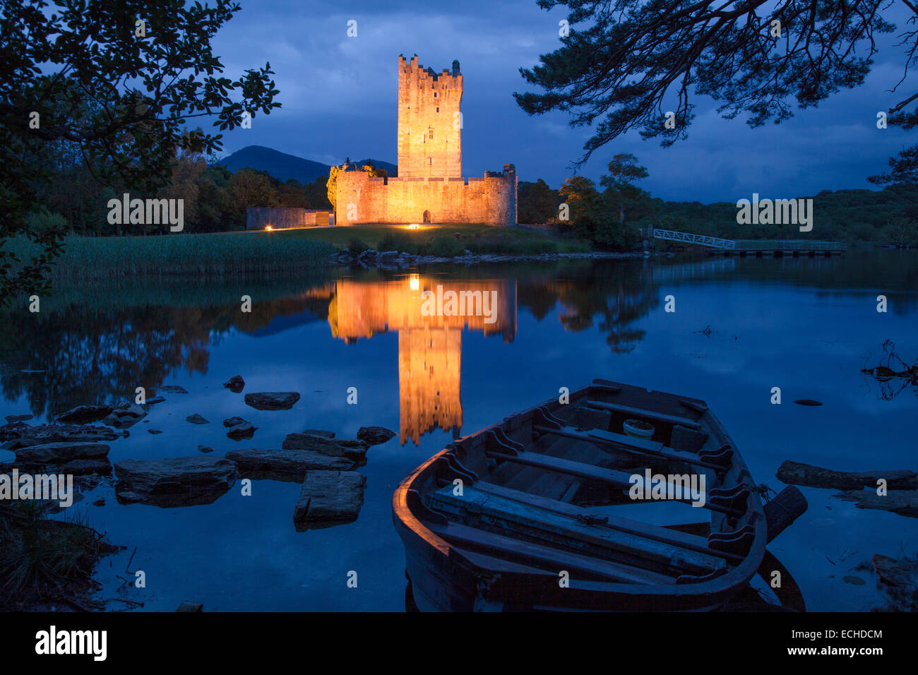 Fishing boat and Ross Castle illuminated at dusk, Lough Leane, Killarney National Park, County Kerry, Ireland. - Stock Image