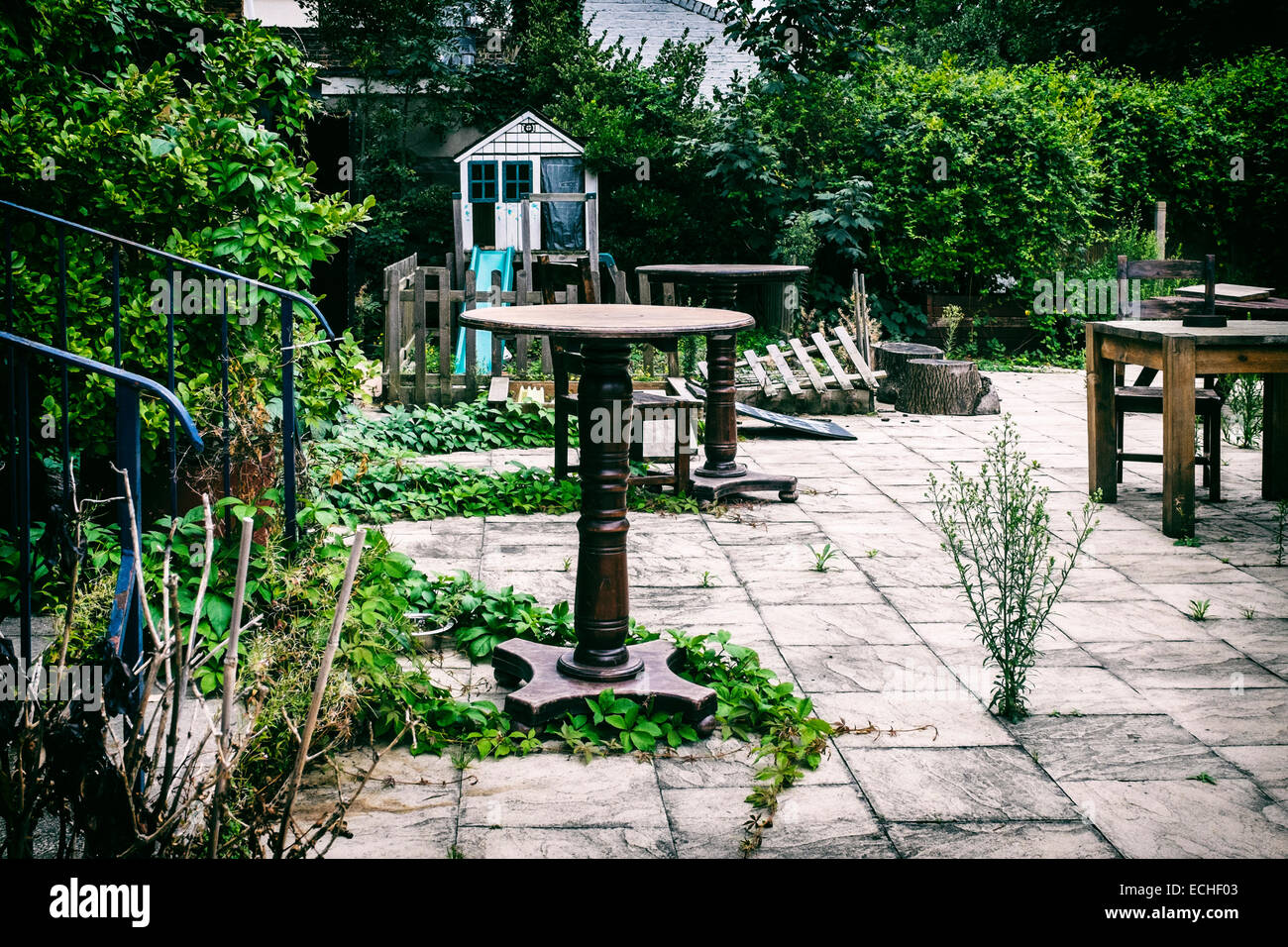 Urban decay - Overgrown garden of closed pub - weeds and dilapidated tables and chairs - Stock Image