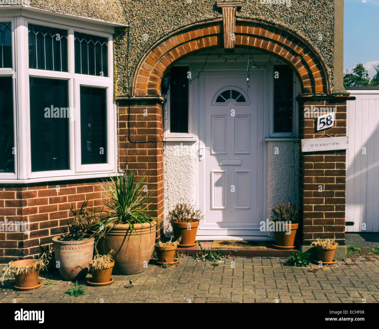 English house exterior - pebble-dash, brick, white door and dead plants in pots - 'it is what it is' sign - Stock Image