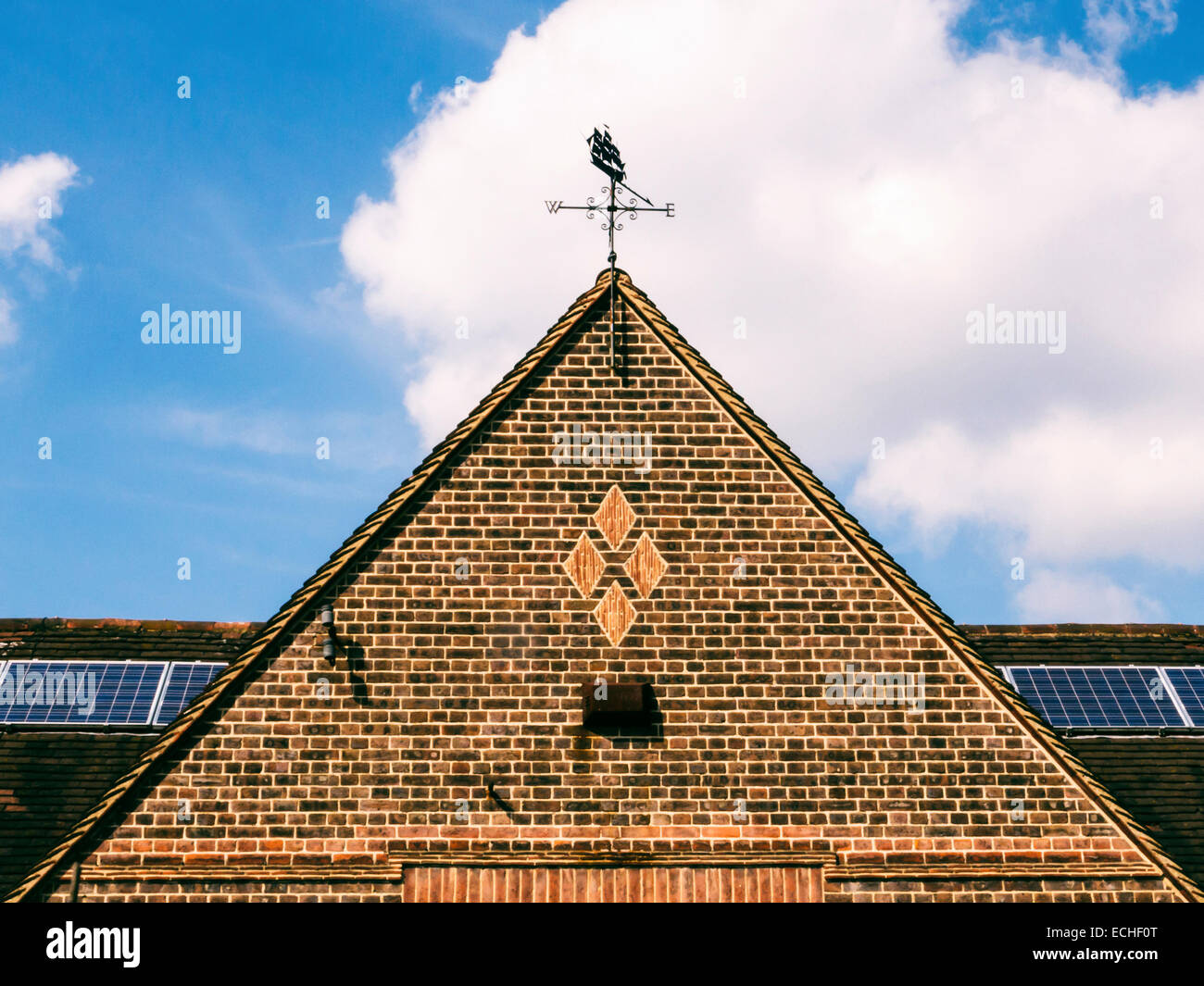 Ship weather vane on brick gable and solar panels on roof of building in Whitton, Twickenham - Stock Image