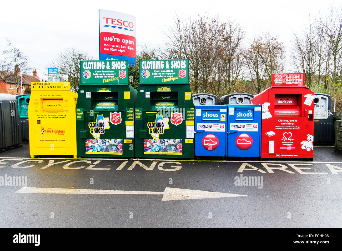 Recycling area charity bins collection collect disposal unwanted clothes shoes British heart foundation salvation - Stock Image