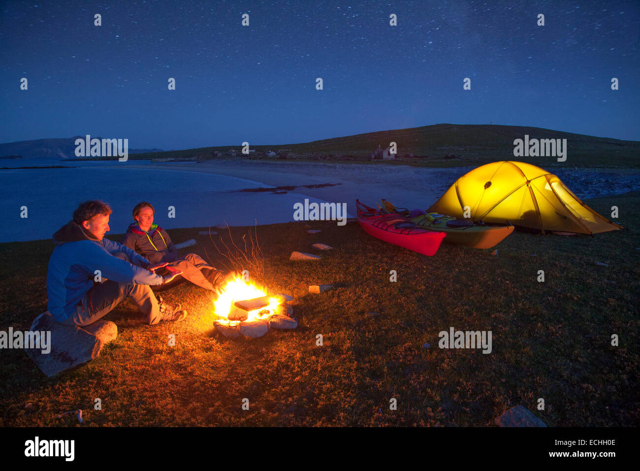 Sea kayakers enjoying an evening campfire on Inishkea South Island, County Mayo, Ireland. - Stock Image