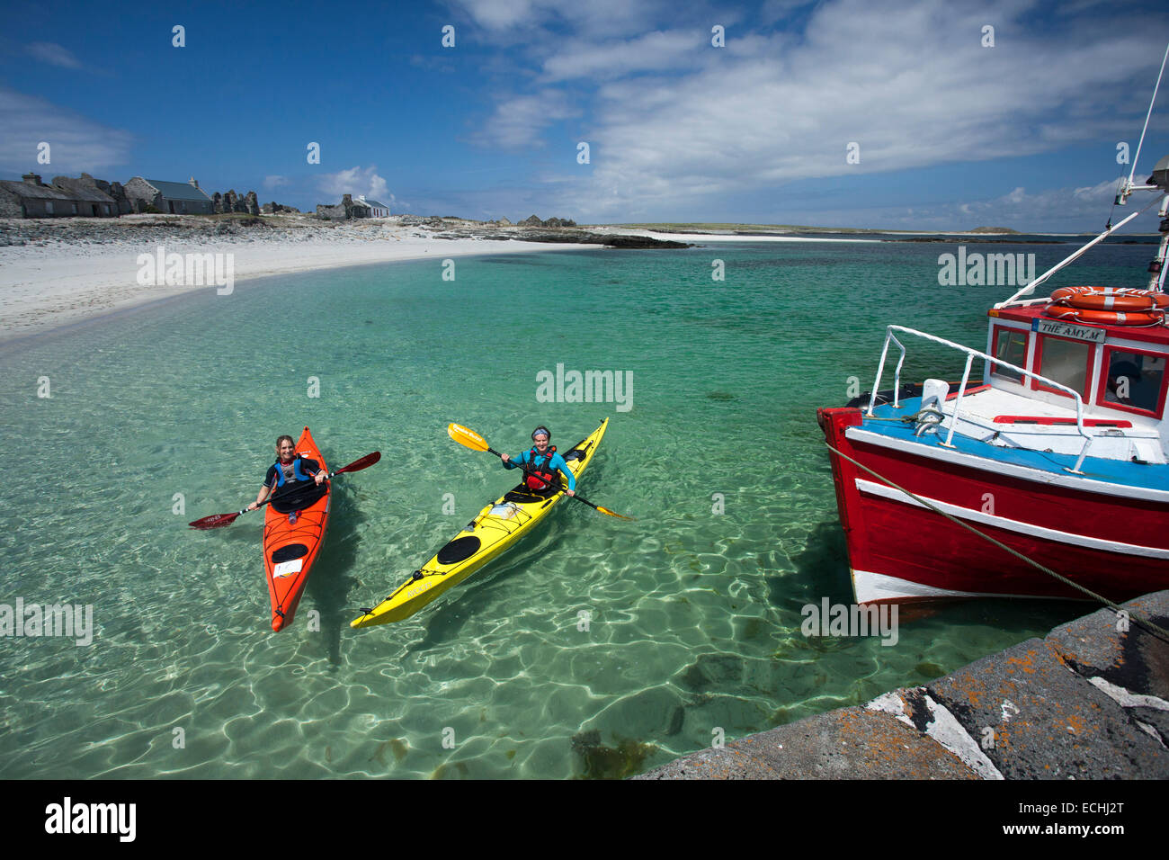 Fishing boat and sea kayakers beside the pier on Inishkea South Island, County Mayo, Ireland. - Stock Image
