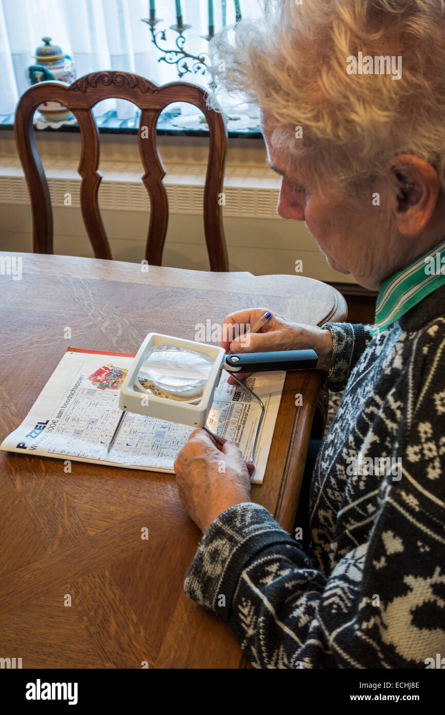 Elderly woman suffering from presbyopia / myopia / short-sightedness looking at crossword puzzle through magnifying - Stock Image