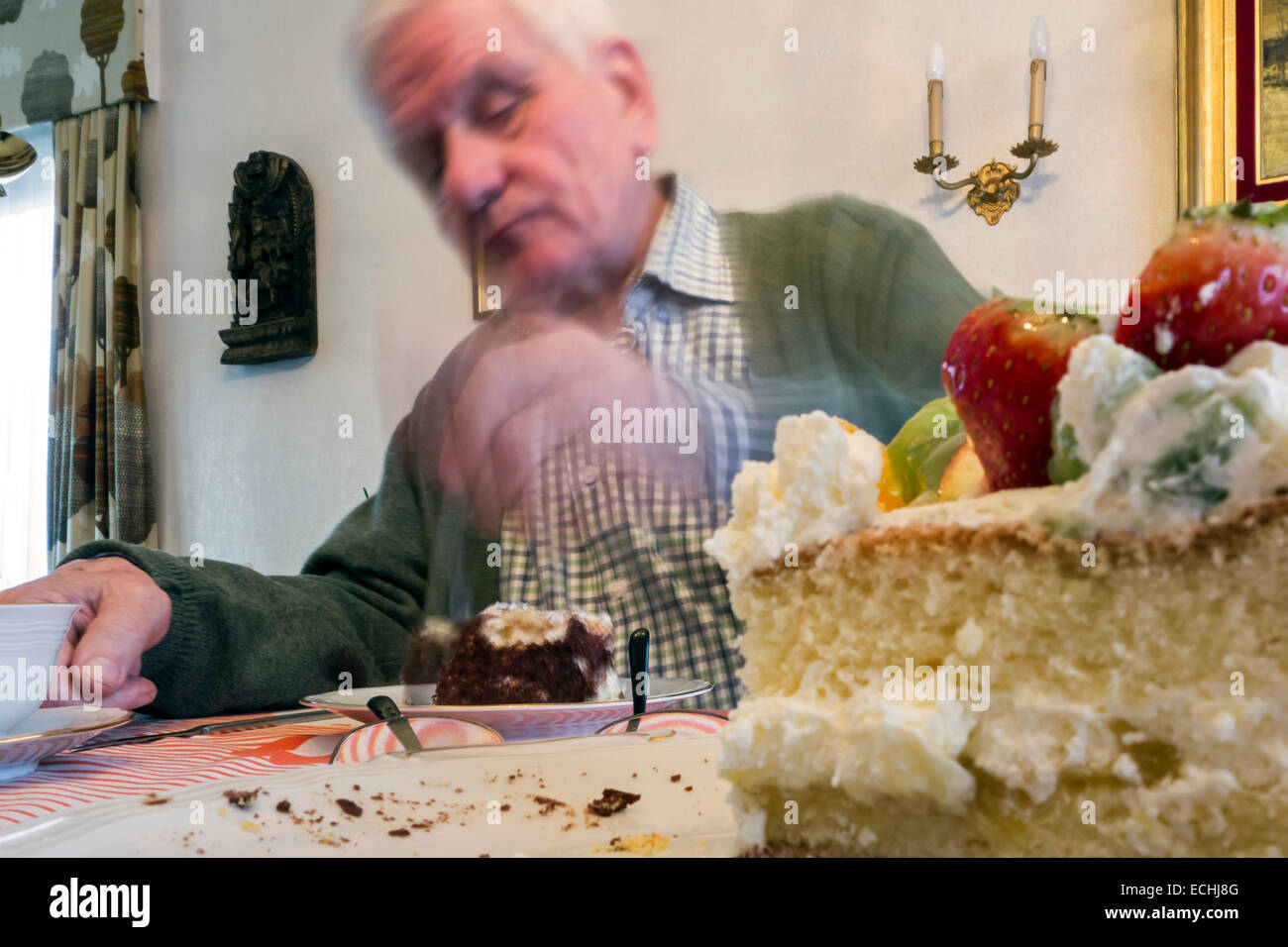Sad looking lonesome elderly man eating birthday cake alone at home in his house - Stock Image