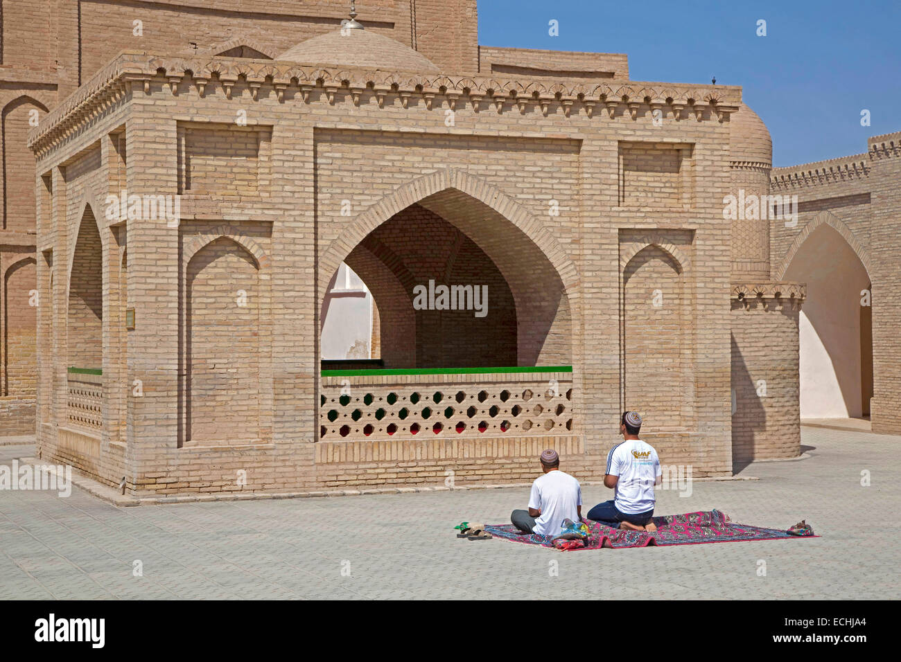 Two Turkmen praying on carpet in front of Mausoleum of Hoja Yusuf Hamadani in the city of Merv / Merw near Mary, - Stock Image