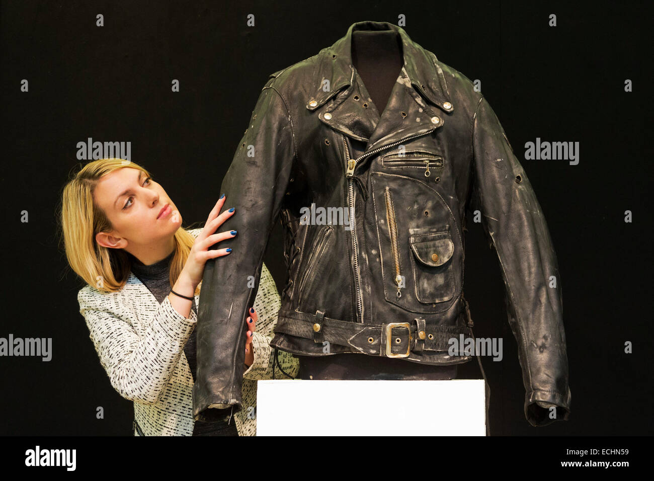 London, UK. 12 December 2014. A Christie's employee looks at a black leather jacket made for Arnold Schwarzenegger - Stock Image