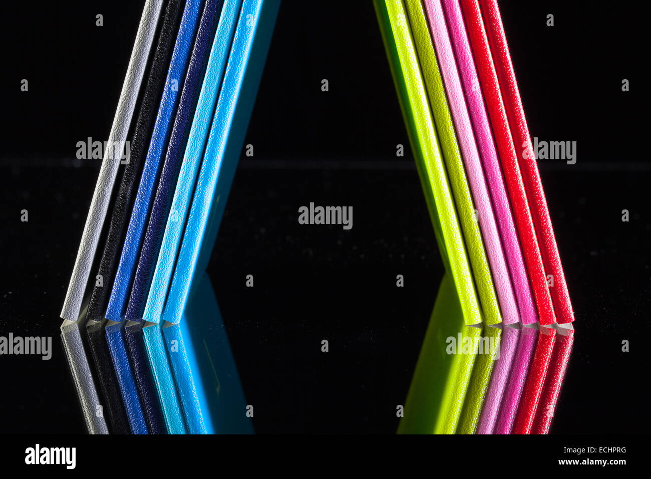 Twelve different colors diaries on a glass desk - Stock Image