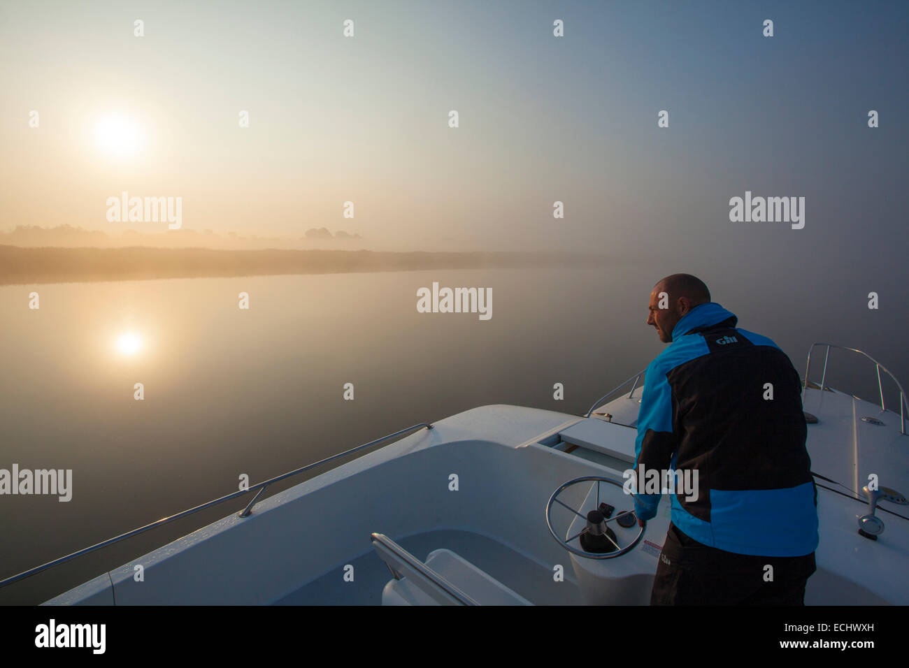 Person navigating a cruise boat across Lough Ree at dawn, River Shannon, County Westmeath, Ireland. Stock Photo