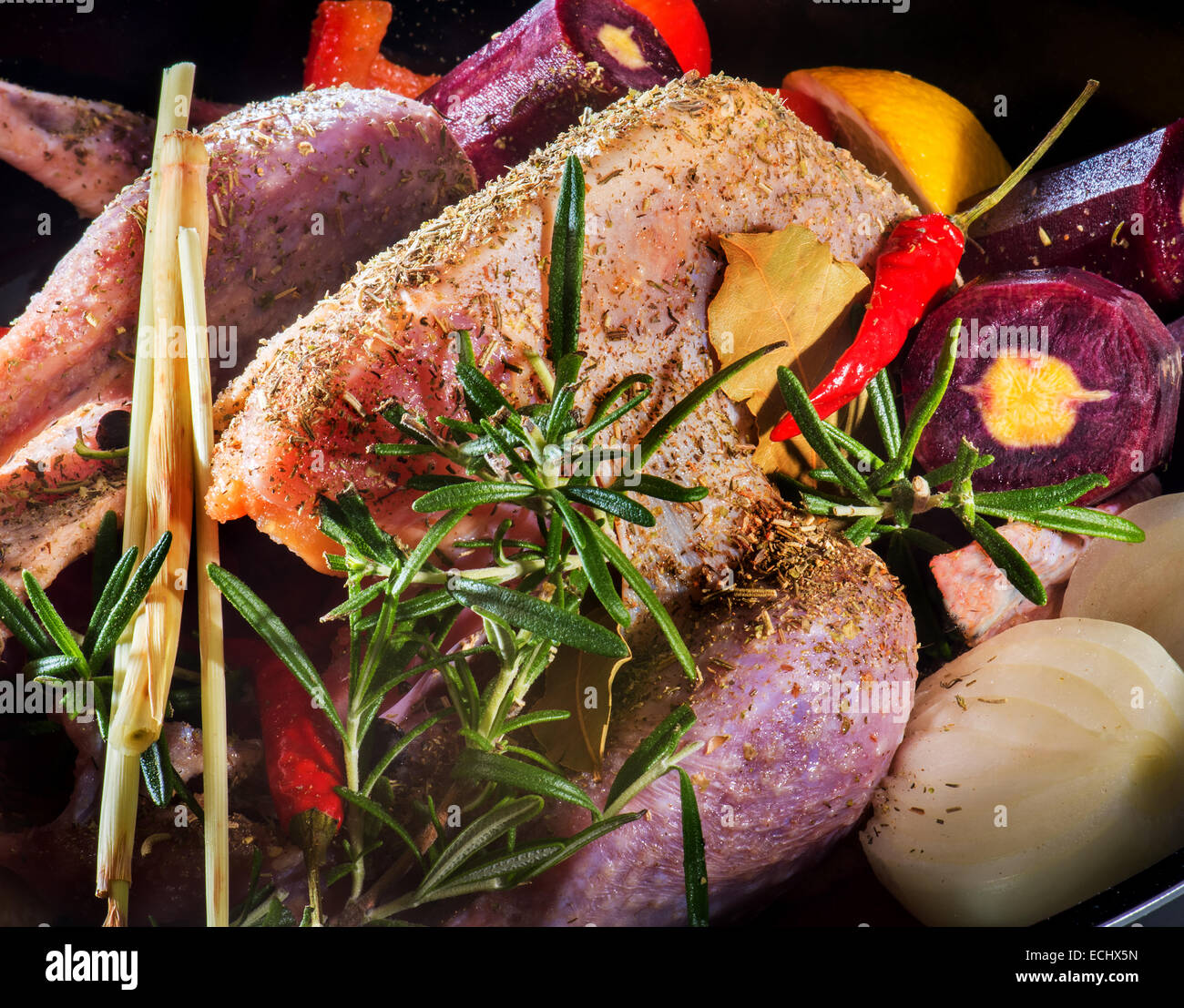 Guinea fowl preparing vegetables for roasting pan. health healthy food herbs spices red peppers carrots celery basil - Stock Image