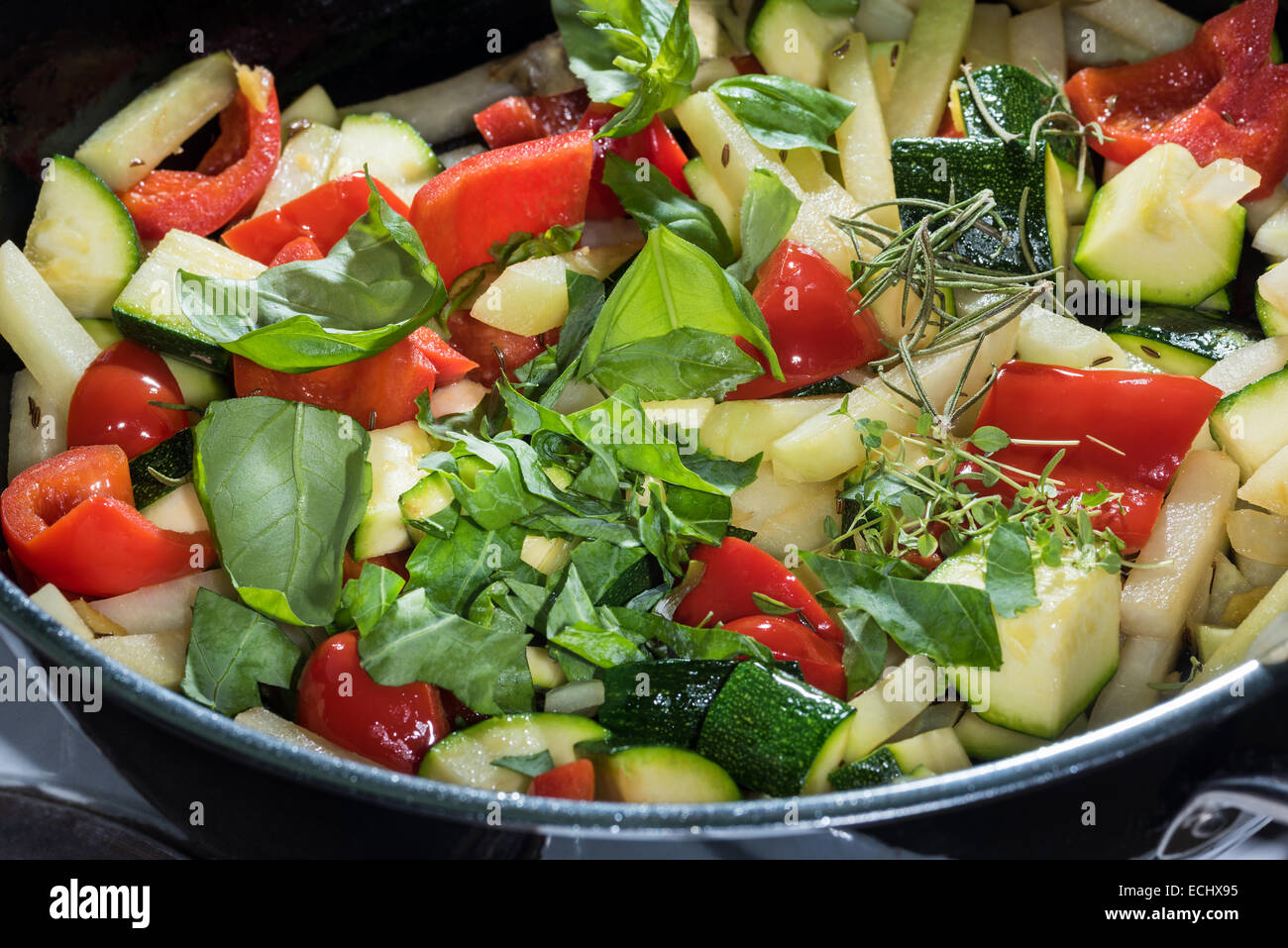 mixed vegetables prepared for frying in a pan. health healthy food herbal spices Zucchine peppers celery basil rosemary - Stock Image