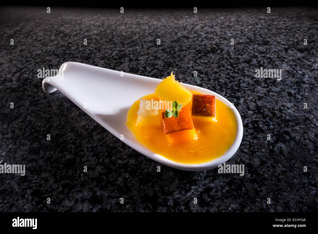 amuse geul Hokkaido Hokkaido pumpkin soup served porcelain spoon FOOD Appetizer chef cook fresh colorful colored - Stock Image