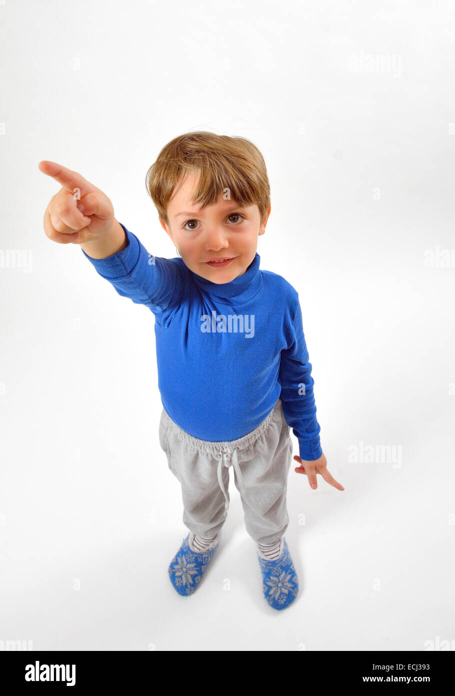 Cheerful little boy pointing up isolated - Stock Image