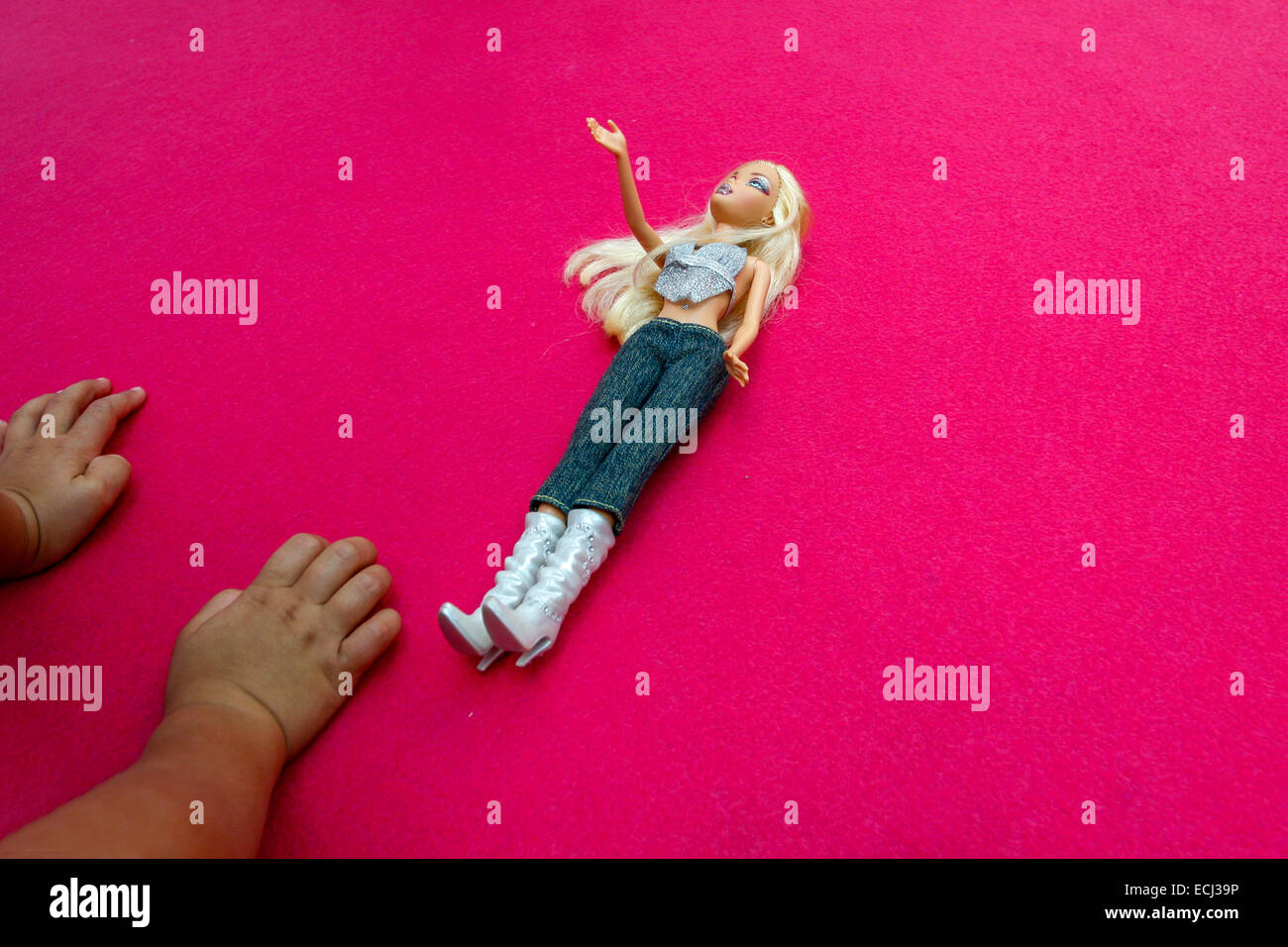 Barbie doll and the child's hands - Stock Image