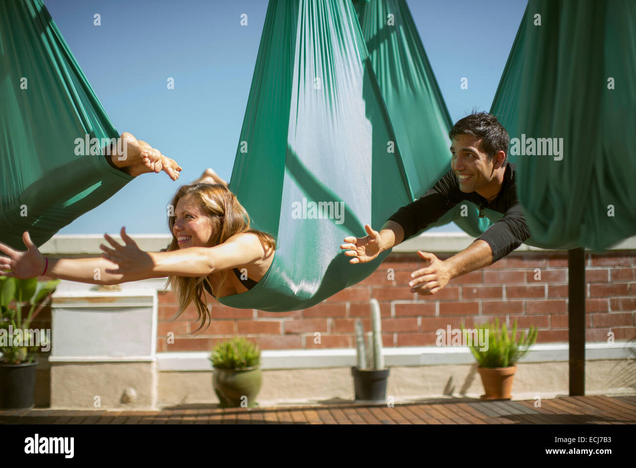A beautiful girl and a young man perform aerial yoga. - Stock Image