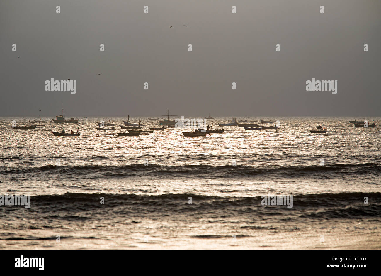 Cluster of fishing boats in dramatic light. - Stock Image