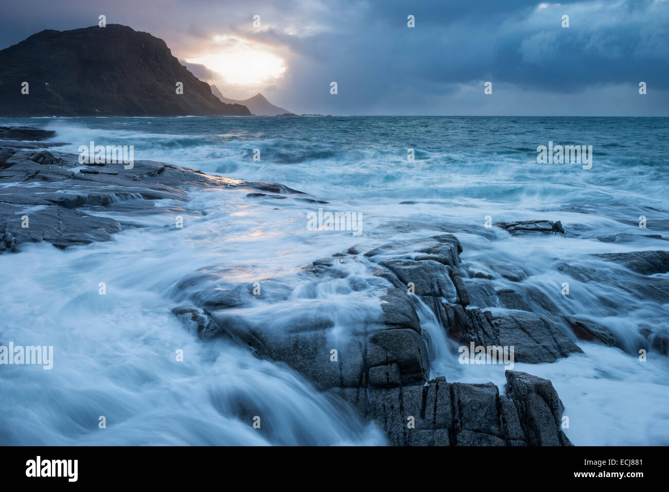 Waves crash over rocky coast of Vestvågøy during winter storm, Lofoten Islands, Norway - Stock Image