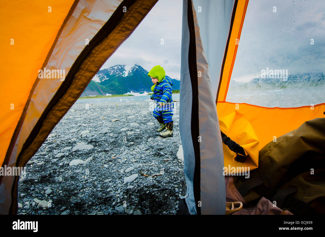 A warmly dressed two year old boy explores outside a tent on a rocky beach next to Bear Lake, Kenai Fjords National - Stock Image