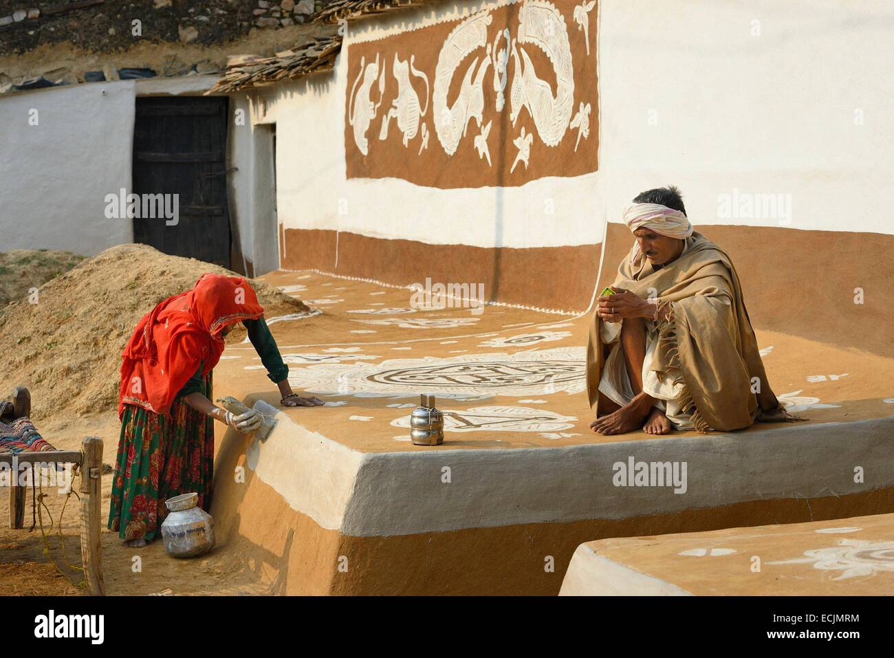 India, Rajasthan, Tonk region, Woman refurbishing her home with a coat of fresh clay prior to Diwali festival. Such - Stock Image